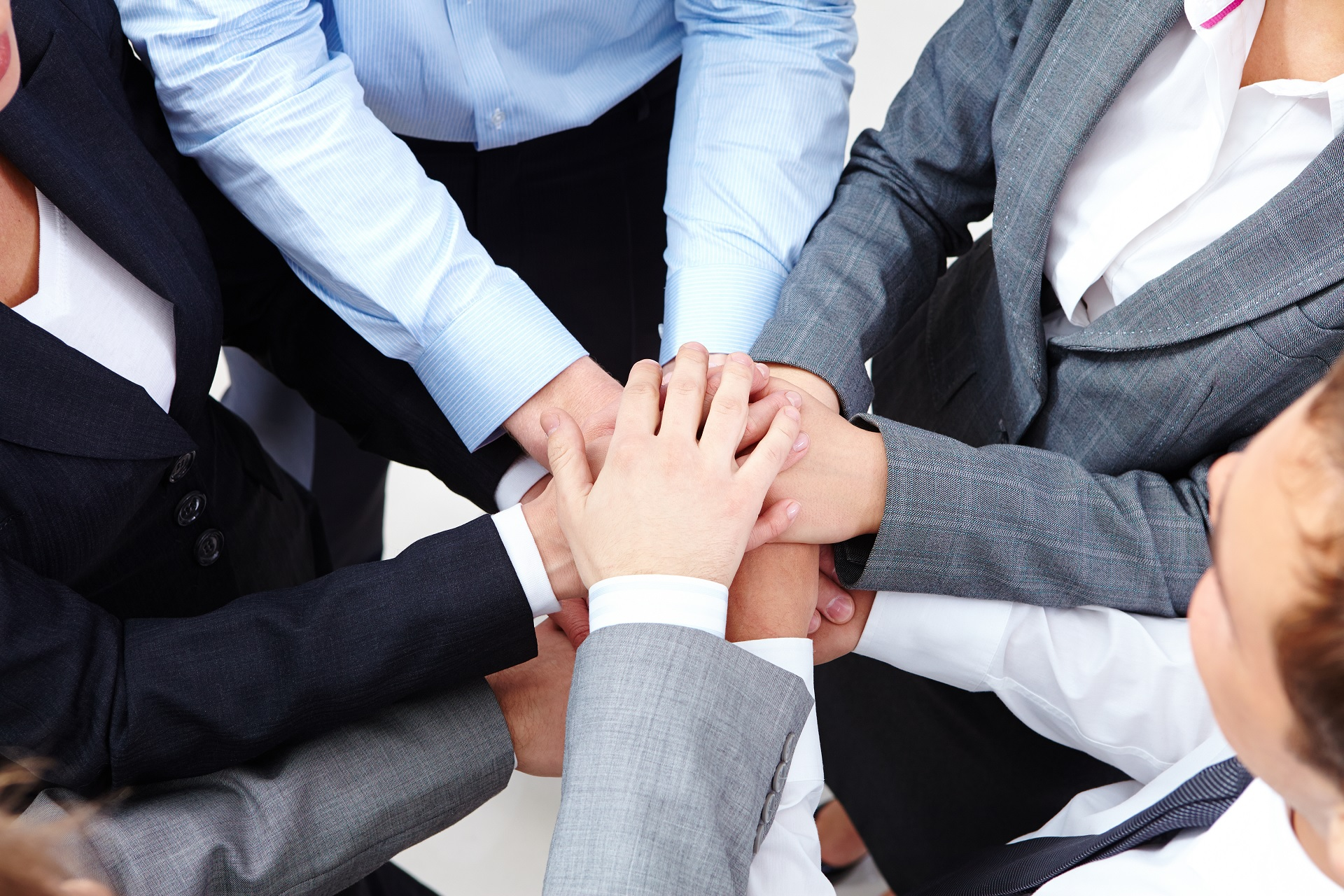 Group of people putting their hands in a circle