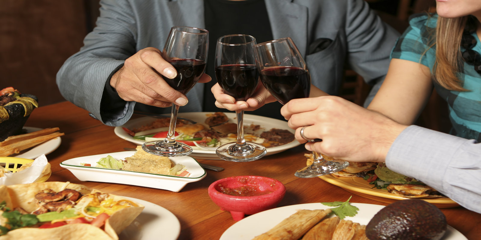 three people toasting with wine at a mexican restaurant