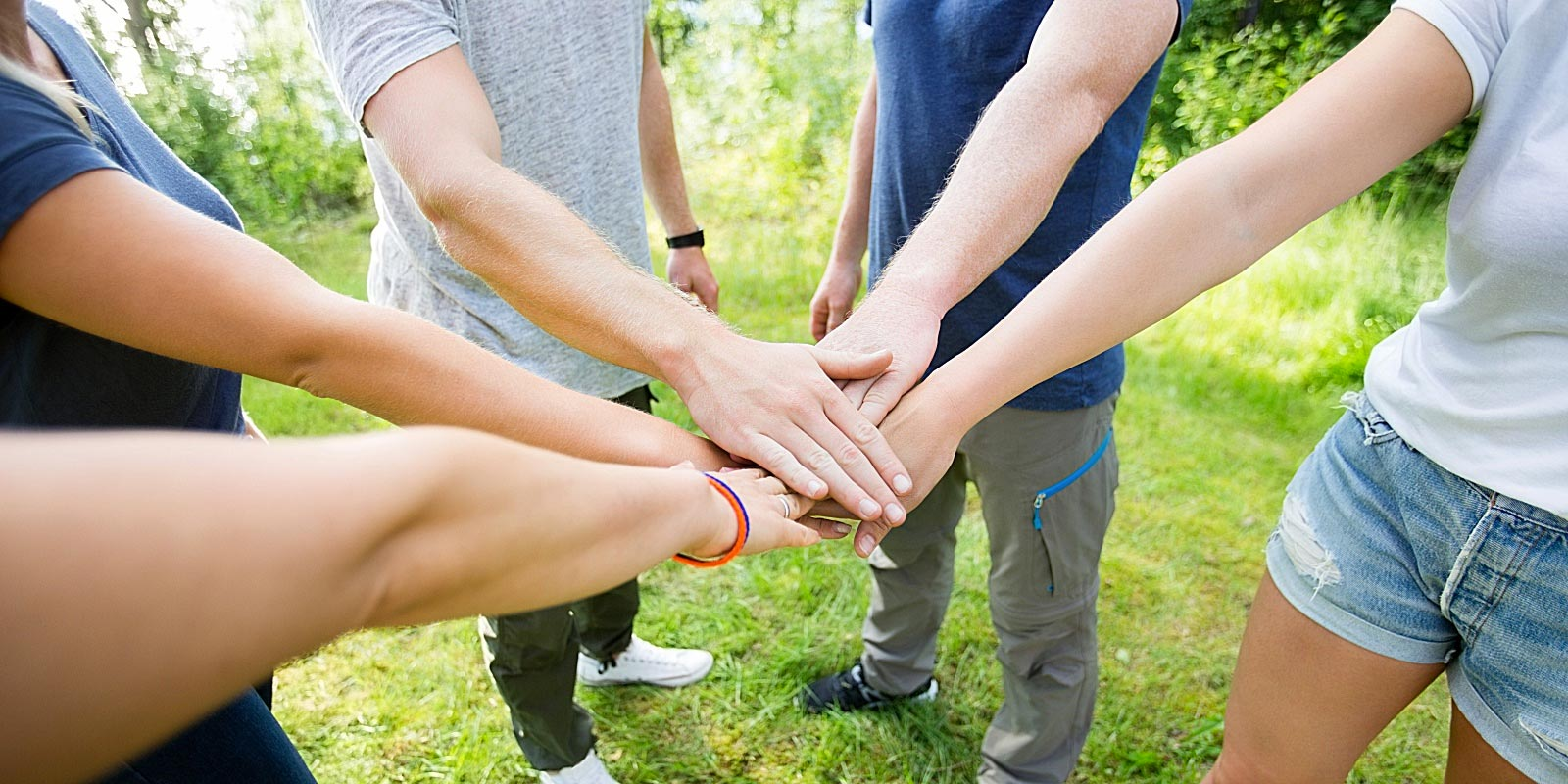 friends putting hands in middle for teamwork
